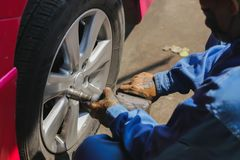 The mechanic is assembling the wheel, put the car in the garage. royalty free stock image