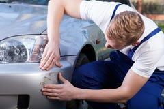 Mechanic assess the damage on the car. Mechanic in uniform assess the damage on the car royalty free stock image