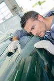 Mechanic assessing finish classic car stock photography
