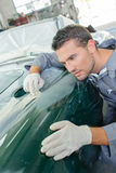 Mechanic assessing wing classic car. Mechanic assessing wing of classic car Stock Image