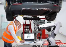 Mechanic with assistance robotic inspection wheel balancing Stock Image