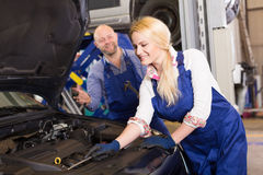 Mechanic and assistant working at auto repair shop Royalty Free Stock Image