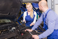 Mechanic and assistant working at auto repair shop Stock Images