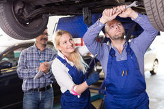 Mechanic and assistant working at auto repair shop Stock Photos