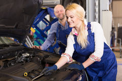 Mechanic and assistant working at auto repair shop Royalty Free Stock Photo