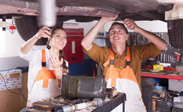 Mechanic and assistant working at workshop Royalty Free Stock Photos
