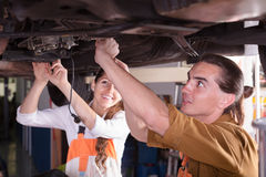 Mechanic and assistant working at workshop Royalty Free Stock Photography