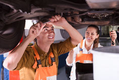 Mechanic and assistant working at workshop Stock Photography