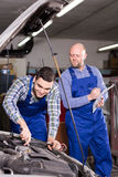 Mechanic assists insurance agent Stock Photography