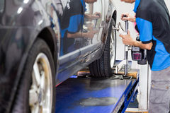 Mechanic attaching the wheel alignment device onto the wheel at workshop. Focus is on the wheel and wheel alignment device Stock Photos