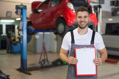 Mechanic in auto repair shop showing blank clipboard Stock Photography