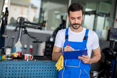 Mechanic in auto repair shop standing Stock Images