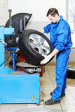 Mechanic at auto wheel tyre changer. Mechanic repairman installing automobile car wheel on tyre changers royalty free stock images