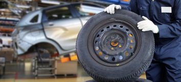 Mechanic with auto wheels. Mechanic man with auto wheels. Worker. Business Stock Photography