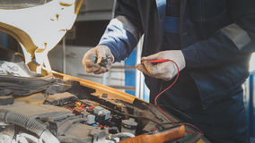 Mechanic in auto workshop works with car electrics - electrical wiring, voltmeter. Close up stock photography
