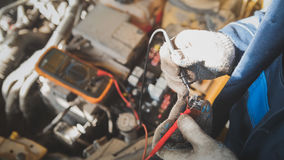 Mechanic in auto workshop works with car electrics - electrical wiring, voltmeter - top view. Close up royalty free stock photo