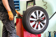 Mechanic balancing a car wheel. On an automated machine checking the readout on the digital display before adding the weights stock photos