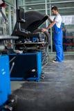 Mechanic balancing  car wheel Stock Photos