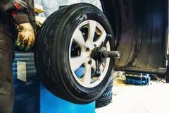 Mechanic balancing wheel with computer machine balancer at car service garage workshop. Toned royalty free stock image