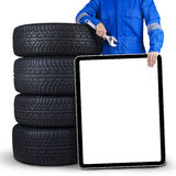 Mechanic with billboard and tires Royalty Free Stock Images