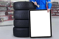 Mechanic with blank board in the garage Royalty Free Stock Image
