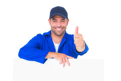Mechanic with blank placard gesturing thumbs up. Portrait of male mechanic with blank placard gesturing thumbs up on white background Royalty Free Stock Photo