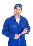 Mechanic in blue overalls holding spanner. Portrait of young male mechanic in blue overalls holding spanner over white stock photos