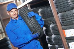 Mechanic holding tire in store warehouse. Mechanic in blue overalls holding tire in the tyre store warehouse Royalty Free Stock Photography