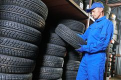 Mechanic pulls tire from the tyre store warehouse. Mechanic in blue overalls pulls tire in the tyre store warehouse Royalty Free Stock Images
