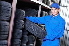 Mechanic pulls tire from the tyre store warehouse. Mechanic in blue overalls pulls tire in the tyre store warehouse Stock Photo