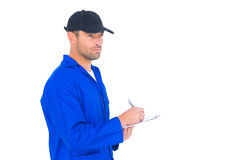Mechanic in blue overalls writing on clipboard. Male mechanic in blue overalls writing on clipboard over white background Stock Photo