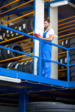 Mechanic in blue uniform checking a stack of tires. While holding a clipboard Royalty Free Stock Photos