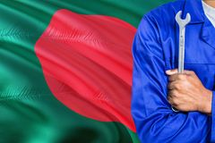 Mechanic in blue uniform is holding wrench against waving Bangladesh flag background. Crossed arms technician stock photos