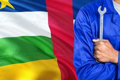 Mechanic in blue uniform is holding wrench against waving Central African Republic flag background. Crossed arms technician.  royalty free stock photos