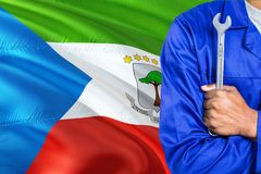 Mechanic in blue uniform is holding wrench against waving Equatorial Guinea flag background. Crossed arms technician.  stock photography
