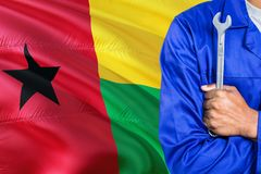 Mechanic in blue uniform is holding wrench against waving Guinea Bissau flag background. Crossed arms technician.  stock image