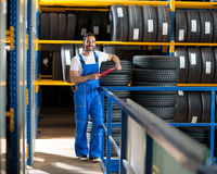 Mechanic in blue uniform standing at stock tyre Stock Photo