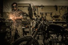 Mechanic building customs motorcycle Royalty Free Stock Image