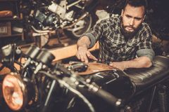 Mechanic building vintage style cafe-racer stock images