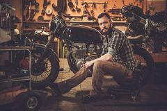 Mechanic building vintage style cafe-racer Stock Image