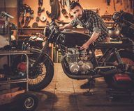 Mechanic building vintage style cafe-racer motorcycle Royalty Free Stock Images