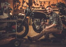 Mechanic building vintage style cafe-racer motorcycle Stock Image