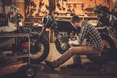 Mechanic building vintage style cafe-racer motorcycle royalty free stock photo
