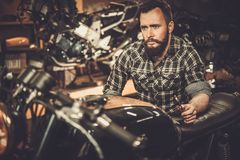 Mechanic building vintage style cafe-racer motorcycle. In custom garage stock photo