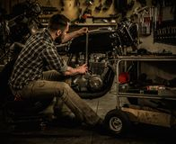 Mechanic building vintage style cafe-racer motorcycle Stock Images