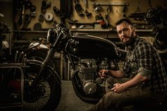 Mechanic building vintage style cafe-racer motorcycle Royalty Free Stock Photography