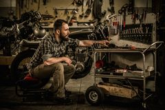 Mechanic building vintage style cafe-racer motorcycle. In custom garage stock images