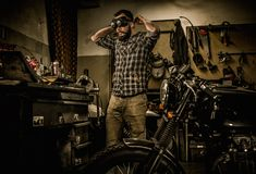 Mechanic building vintage style cafe-racer motorcycle Stock Photography
