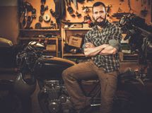 Mechanic building vintage style cafe-racer motorcycle Stock Photos