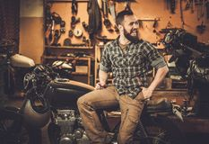 Mechanic building vintage style cafe-racer motorcycle. Rider and his vintage style cafe-racer motorcycle in customs garage royalty free stock image